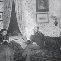 Rev. R. M. Chipman (?), seated, reading book.