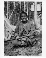 Ojibwa woman, portrait, kneeling outside