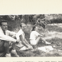The Carlsons and Patsey Taylor, sitting outdoors on grass.