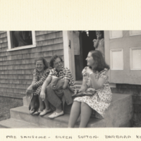 Mrs. Sansome, Eillen Sutton, Barbara Korsch sitting on steps outside of building.