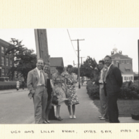 Ugo and Lilla Fano, Mrs. Sax, Mrs. Carlson, Carlson and Sax standing outside on sidewalk with buildings in background.