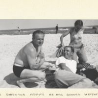 Demerec on the beach in bathing suit with man and woman.