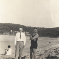 Two men standing on beach, one in swimming suit, one wearing a tie.