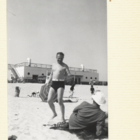 Demerec walking on beach in bathing suit, talking to unidentified man.