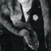 Half length view of unidentified woman, wearing mink shawl and white gloves.