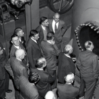 Group of unidentified men examining equipment.