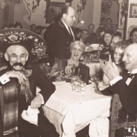 "Simon Flexner, two women, and a man wearing a sombrero and fake mustache sitting, informal, in the ""El Chico"" restaurant in New York city."