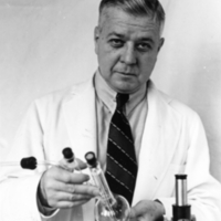 Thomas M. Rivers, holding test tubes.