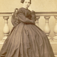 Sophie Boas, seated, wearing full hoop skirt.