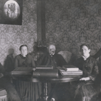Boas family, seated, around table.