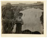 24: Man and boy standing next to stretched hide